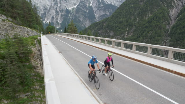 aerial  couple road cycling across a nice bridge in the mountains - road marking stock videos & royalty-free footage