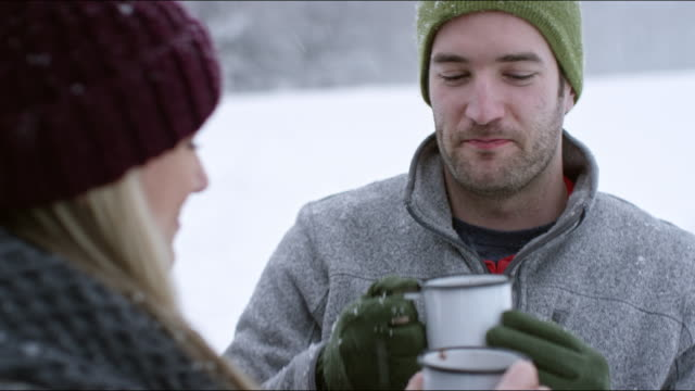 Couple roasting marshmallows and sharing hot cocoa around a campfire