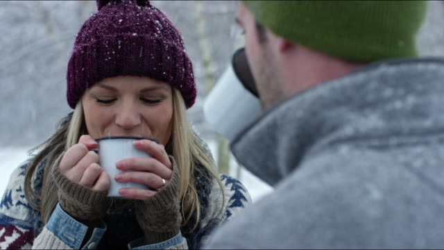 stockvideo's en b-roll-footage met couple roasting marshmallows and sharing hot cocoa around a campfire - muts