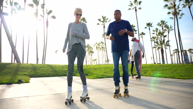 ms couple roller skating together with friends in park - confidence stock videos & royalty-free footage
