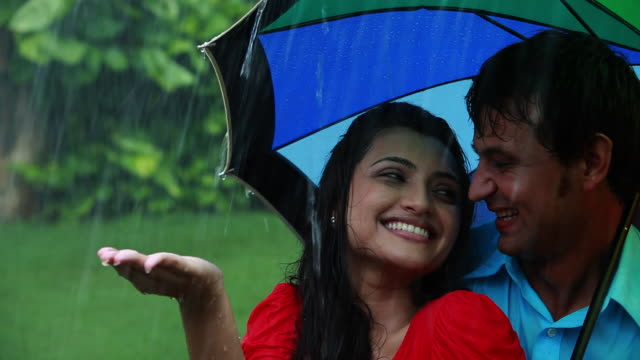 couple romancing under an umbrella in the rain  - falling in love stock videos & royalty-free footage