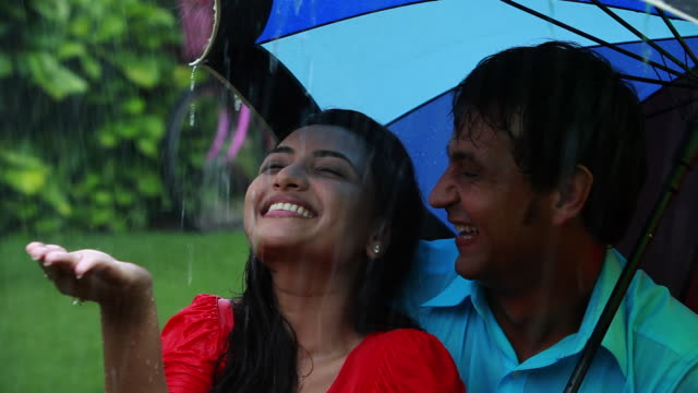 couple romancing under an umbrella in the rain  - falling in love stock videos and b-roll footage