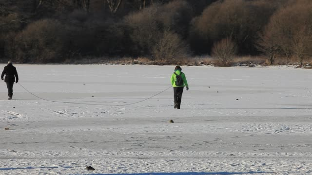 a couple roped together walking on ice when derwent water froze over in winter lake district uk - rope stock videos & royalty-free footage