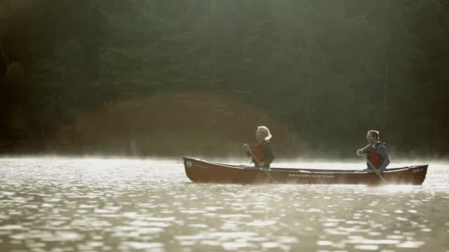 vídeos y material grabado en eventos de stock de  ws couple rowing a boat across a lake / stowe, vermont, united states - pareja de mediana edad
