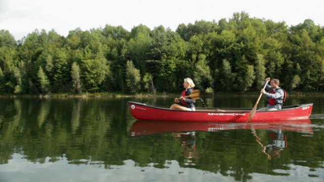 vidéos et rushes de  ws couple rowing a boat across a lake / stowe, vermont, united states - couple d'âge moyen