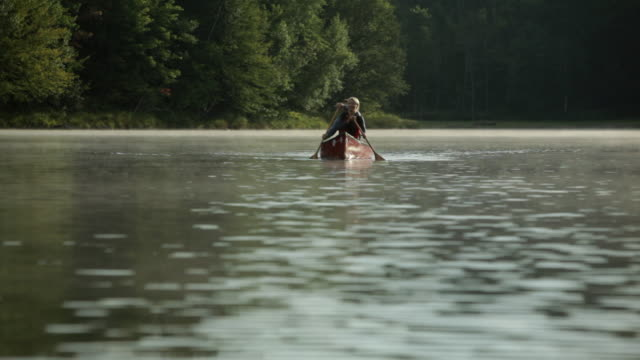 WS Couple rowing a boat across a large lake / Stowe, Vermont, United States