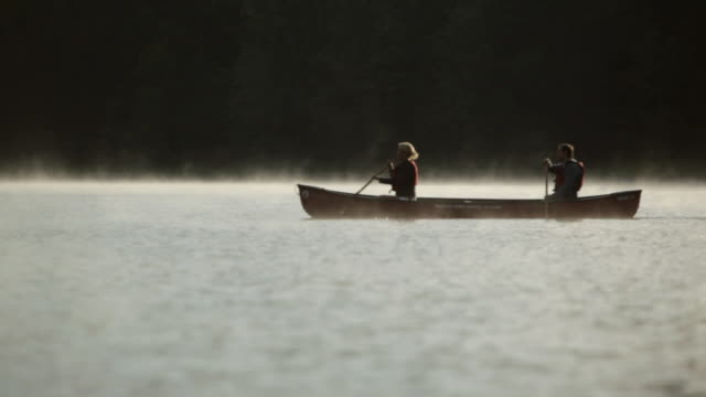 WS Couple rowing a boat across a misty lake / Stowe, Vermont, United States