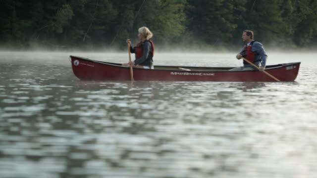 vídeos y material grabado en eventos de stock de  ws couple rowing boat across lake / stowe, vermont, united states - pareja de mediana edad