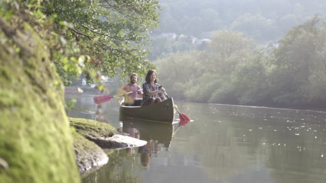 couple rowing boat in lake - wales stock videos & royalty-free footage