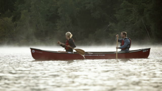 MS Couple rowing canoe on a misty lake at sunrise / Stowe, Vermont, United States