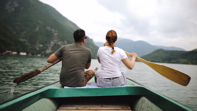 couple rowing rowboat together on lake - using a paddle stock videos & royalty-free footage