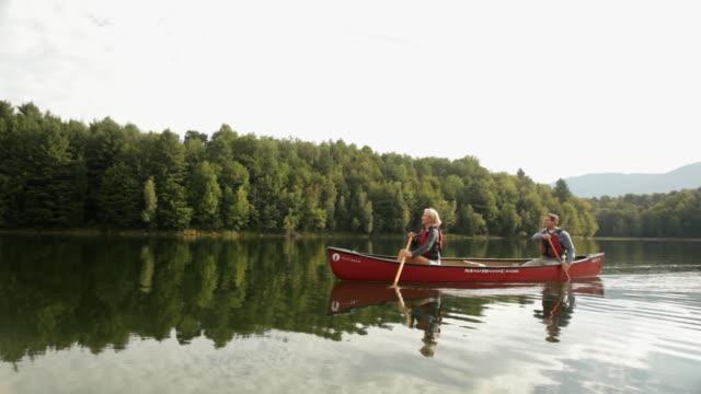 vidéos et rushes de  ws couple rowing their canoe across a large lake / stowe, vermont, united states - couple d'âge moyen