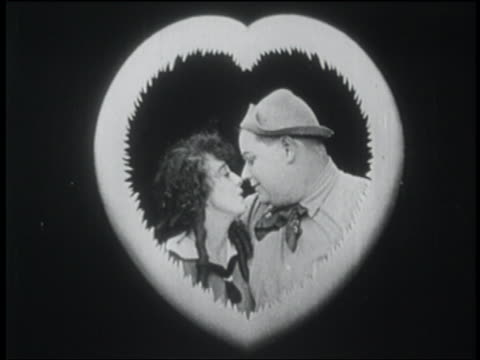 b/w 1916 couple rubbing noses + kissing framed by heart - verlieben stock-videos und b-roll-filmmaterial