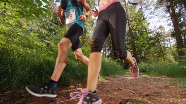 SLO MO CS Couple running a marathon on a forest trail