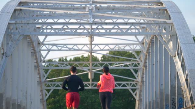 vídeos y material grabado en eventos de stock de a couple running across a bridge. - slow motion - pareja de mediana edad