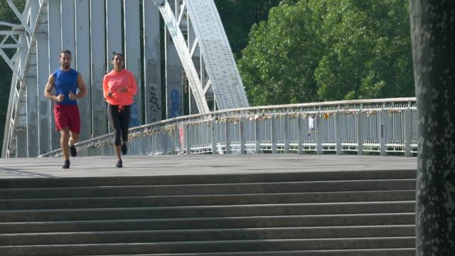 vidéos et rushes de a couple running across a bridge. - slow motion - couple d'âge moyen