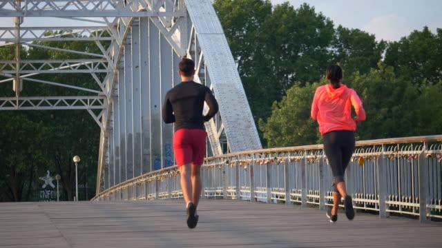 a couple running across a bridge. - coppia di adulti di mezza età video stock e b–roll