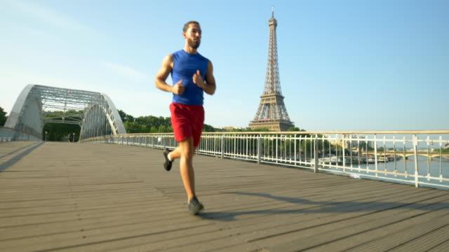 a couple running across a bridge with the eiffel tower. - coppia di adulti di mezza età video stock e b–roll