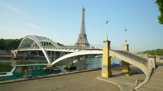 a couple running across a bridge with the eiffel tower. - eiffel tower paris stock videos & royalty-free footage
