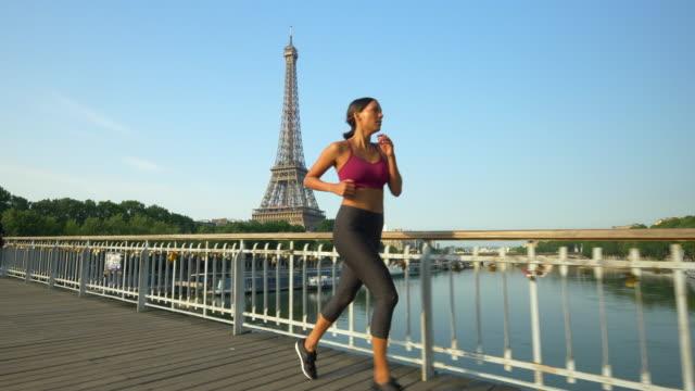 vidéos et rushes de a couple running across a bridge with the eiffel tower. - jogging