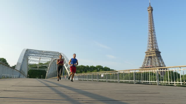 a couple running across a bridge with the eiffel tower. - フランス点の映像素材/bロール