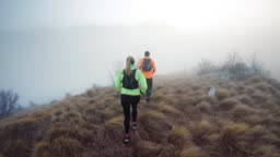 Couple running across a foggy mountain on a grassy trail