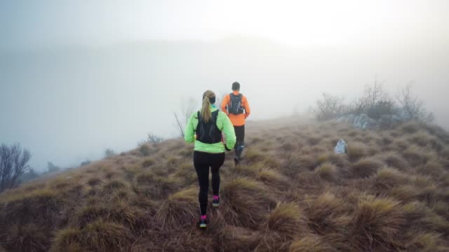 couple running across a foggy mountain on a grassy trail - backpack stock videos & royalty-free footage