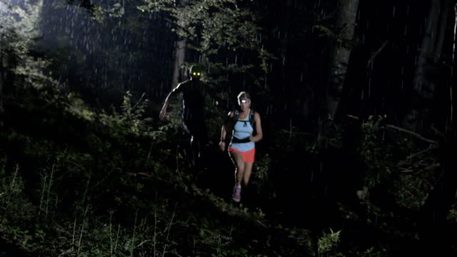 SLO MO Couple running across the forest on a rainy night