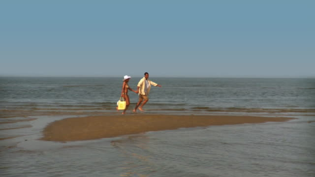 ws pan couple running along beach in shallow water, eastville, virginia, usa - eastville stock videos and b-roll footage