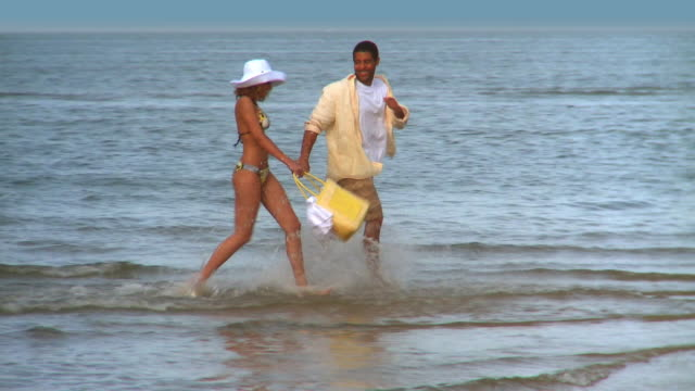 ms pan couple running along beach in shallow water, eastville, virginia, usa - eastville stock videos and b-roll footage