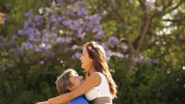 couple running and hugging in park - 膝から上の構図点の映像素材/bロール