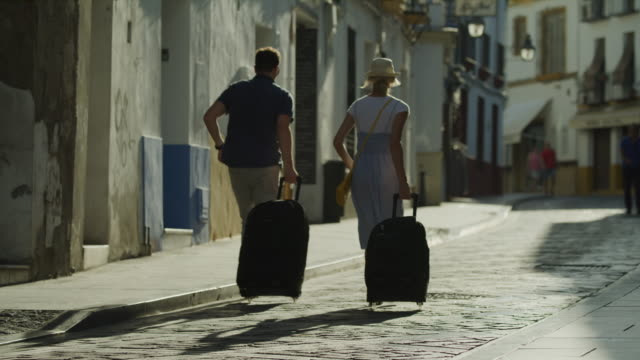couple running and pulling suitcases uphill on street in city / cordoba, cordoba, spain - rolling stock videos & royalty-free footage