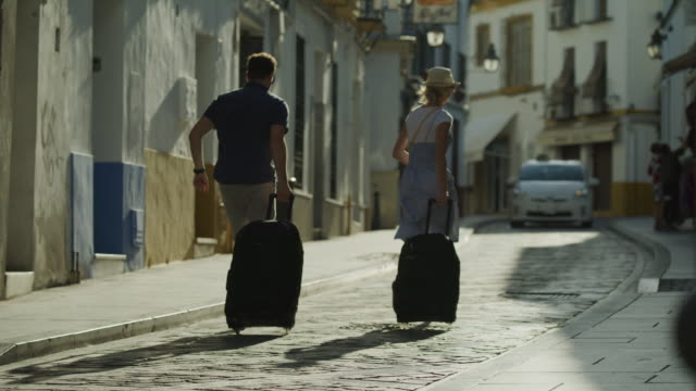 couple running and pulling suitcases uphill on street while hailing taxi / cordoba, cordoba, spain - taxi video stock e b–roll