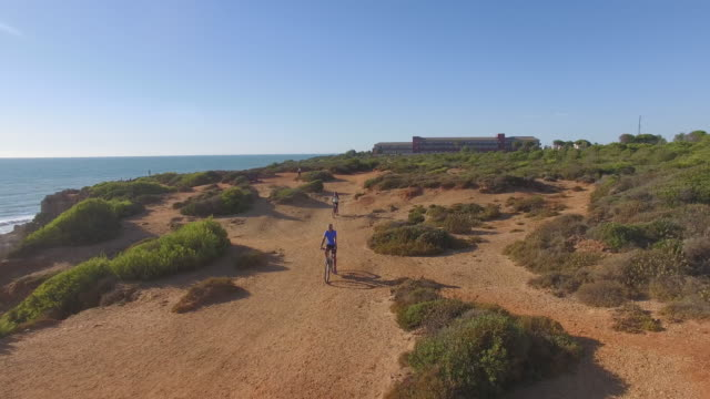 stockvideo's en b-roll-footage met couple running bike near to the sea - silvestre
