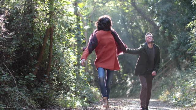 couple running in forest in fall - オーバーコート点の映像素材/bロール