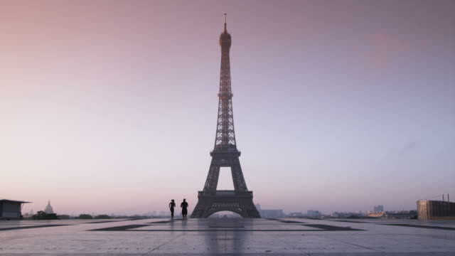 vidéos et rushes de couple running in front of the eiffel tower - matin