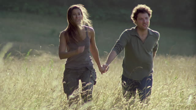MS, Couple running in high grass meadow, Saint Ferme, Gironde, France