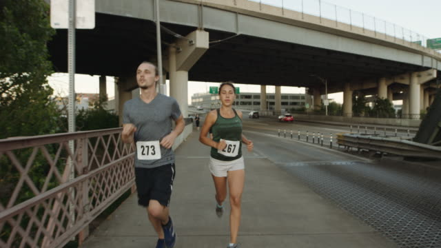 uhd 4k: slo mo paar laufen marathon - marathon stock-videos und b-roll-filmmaterial