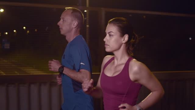 vídeos de stock, filmes e b-roll de slo mo t casal correndo na cidade à noite - camiseta