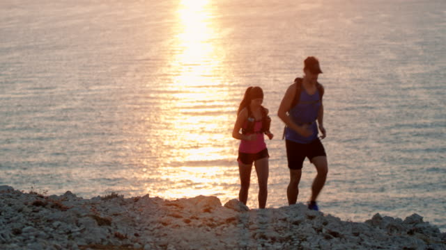 couple running on a rocky trail above the sea at sunset - sun visor stock videos & royalty-free footage