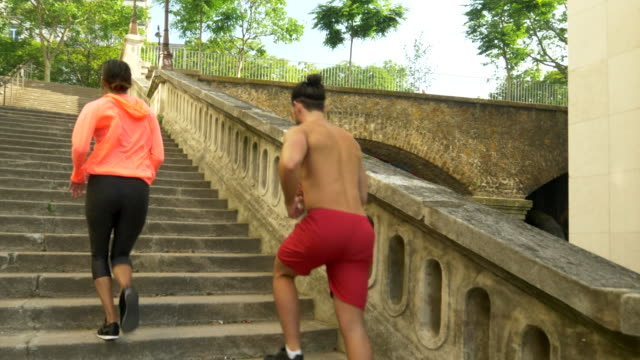 a couple running on stairs in a city as a workout. - slow motion - geographical locations stock videos & royalty-free footage