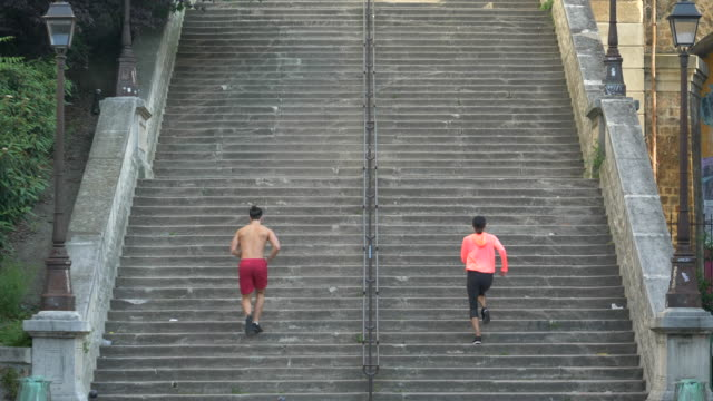 a couple running on stairs in a city as a workout. - goodsportvideo stock videos and b-roll footage