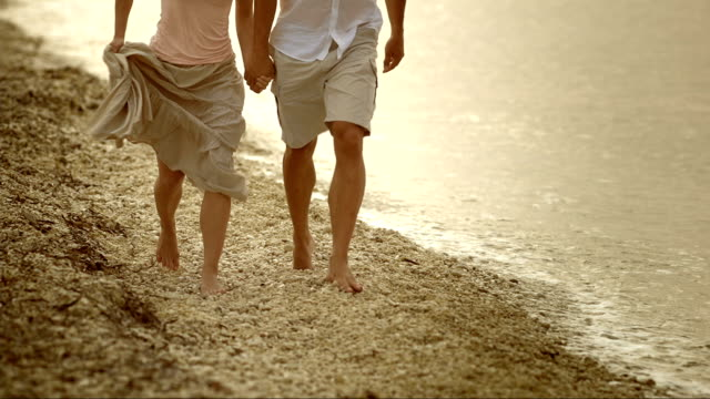 vídeos y material grabado en eventos de stock de una persona pareja corriendo en la playa al atardecer - falda