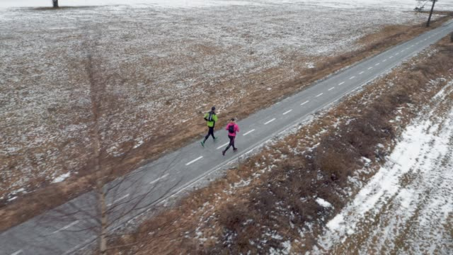 AERIAL Couple running on walkway on a cold winter day