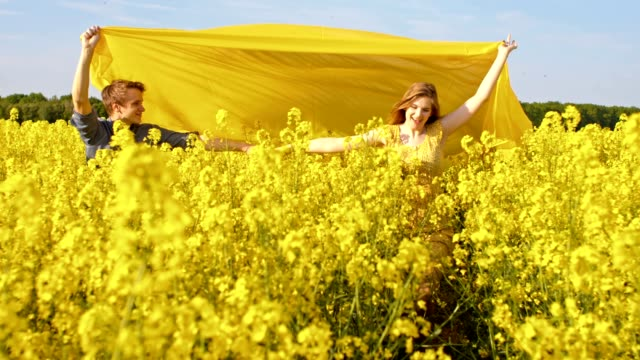 SLO MO Couple running through a field of blooming canola
