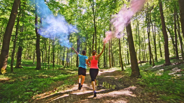 slo mo ts couple running through the forest with blue and red smoke flares - relay stock videos and b-roll footage