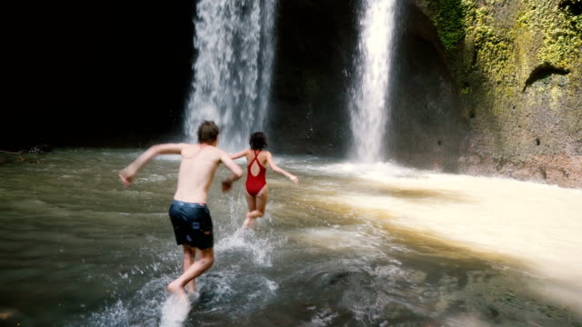 couple running to   swim  in  waterfall in bali, indonesia - waterfall stock videos & royalty-free footage