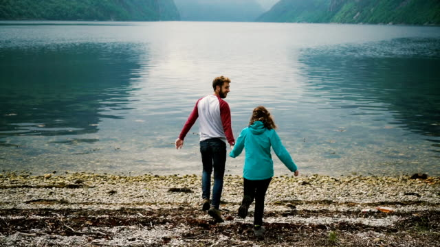 Couple running to the fjord  in Norway