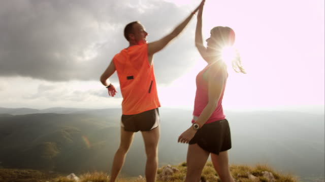 ts couple running to the top and raising hands - top garment stock videos & royalty-free footage
