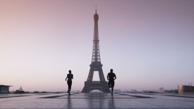 couple running towards the eiffel tower - morning exercise stock videos & royalty-free footage